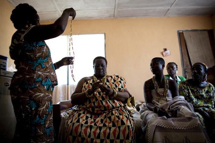 OTUAM, GHANA- OCTOBER 3: Royal dresser, Grace Bentil, 48 (L) places traditional jewelry on King Peggielene